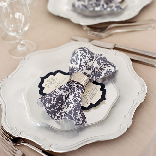 Baroque style plates with navy damask napkins in silver napkin rings came together to create stately place settings.