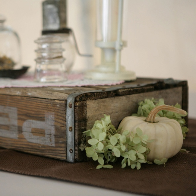 Reception centerpieces included vintage crates and knick-knacks as well as white pumpkins and green hydrangeas.