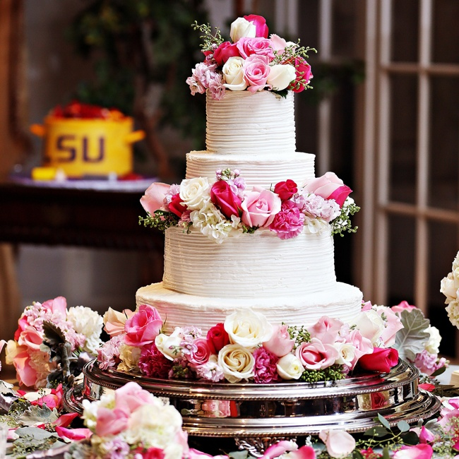 The four-tiered cake featured combed buttercream frosting and a ring of pink and white roses around each layer.