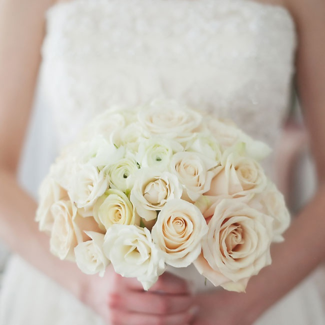 The bride's simple, all-white bridal bouquet was filled with roses and ranunculuses.
