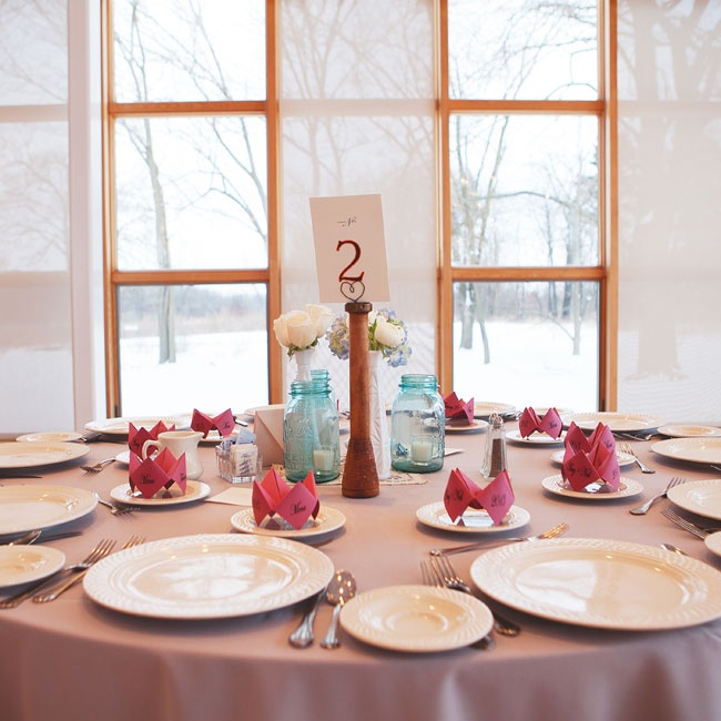 The reception tables were topped with an eclectic mix of vintage Mason jars, milk glass vases and tea lights that the bride found at various thrift stores. The red menu cards were hand-folded into fortune tellers and sat at each place setting.