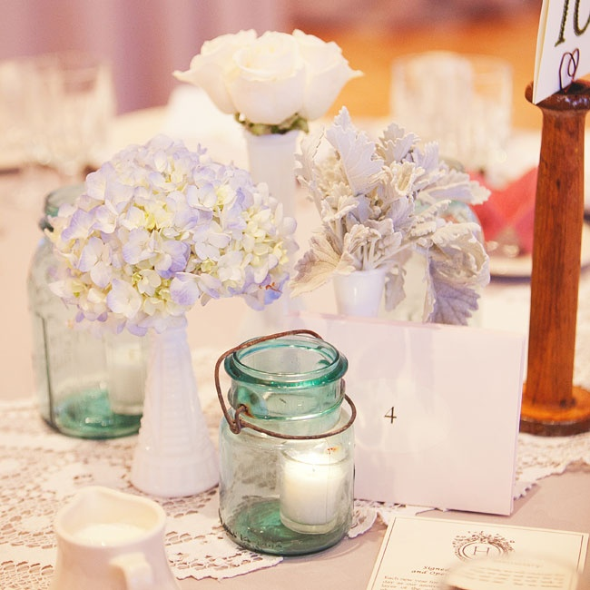 Milk glass vases held blue hydrangeas, dusty miller and white roses. Vintage blue Mason jars served double-duty as votive holders, and cast a soft glow on the tables.