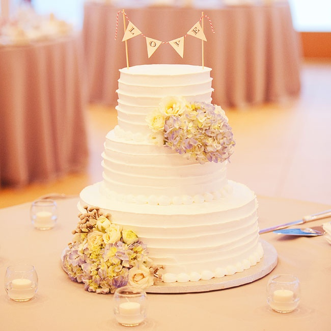 A sweet pennant decorated the top of the three-tier buttercream wedding cake.