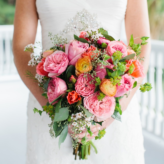 Jessica carried a bright bouquet of coral, pink and orange flowers including peonies, roses and ranunculuses. Eucalyptus and flowering spurge accented the bouquet.