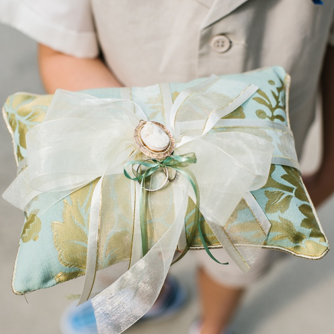 The couple chose a ring pillow made with a robin's egg blue and pale green fabric in a floral pattern. Organdy ribbon and a Victorian-style charm for an elegant touch.