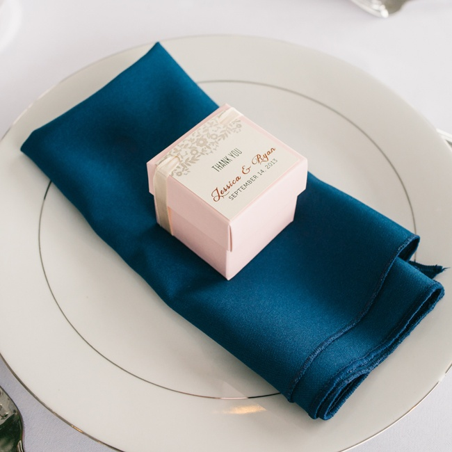 The tables were set with gold accented white plates and navy linens. The couple placed favors in small pale pink boxes at each place setting.