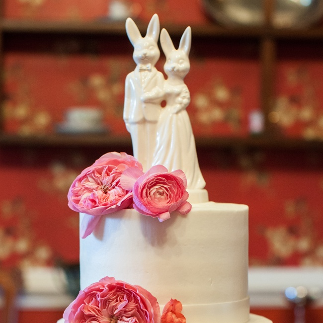Jessica and Ryan's white fondant cake was topped with a porcelain rabbit bride and groom cake topper and two bright pink peonies.