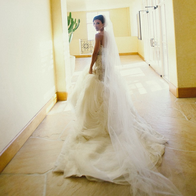 The bride upped the drama of her draped Lazaro gown with a cathedral-length ivory veil.
