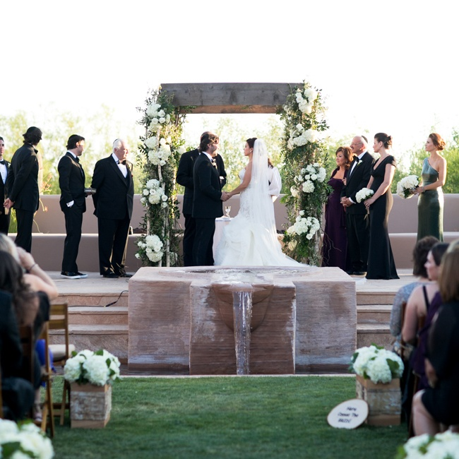 The couple exchanged vows on an elevated outdoor patio on top of a decorative waterfall.