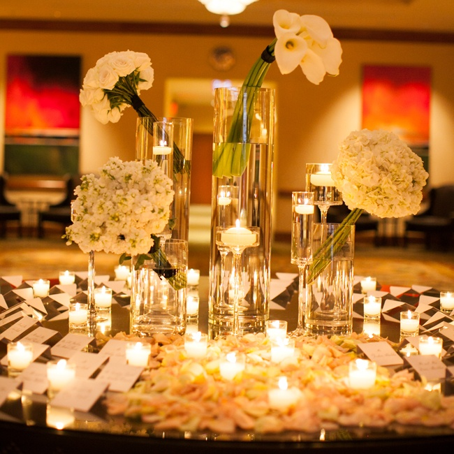The reception escort cards were set out on a circular table decorated with lit candles and clusters of peonies, hydrangeas and calla lilies.