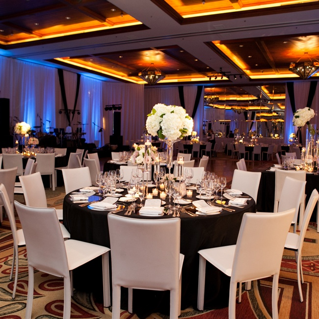 The couple's chic indoor reception was backlit with blue lighting and featured modern, white chairs and place settings next to dark navy tablecloths.