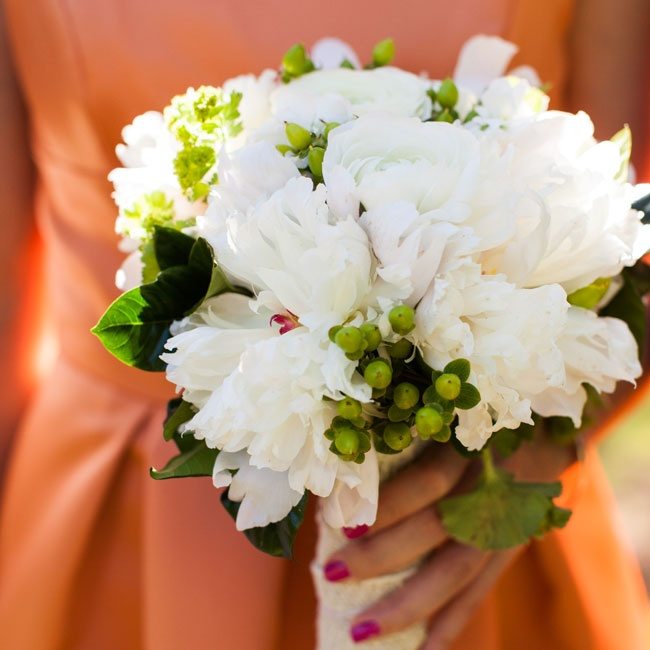 White peonies and ranunculus were paired with green hypericum berries and lady's mantle for a touch of contrast to the orange dresses.