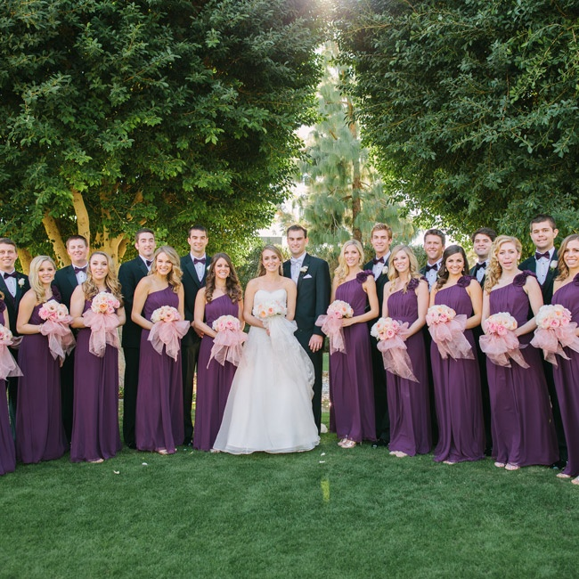 Christine's bridesmaids wore formal floor-length chiffon gowns with asymmetrical one-shoulder necklines in a deep purple hue. The groomsmen wore formal black tuxedos with purple bow ties to complement the girls' dresses.