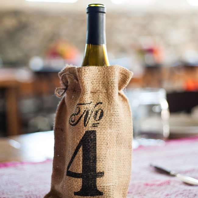 Burlap bags, stamped with numbers, held wine bottles and served double-duty as table numbers.