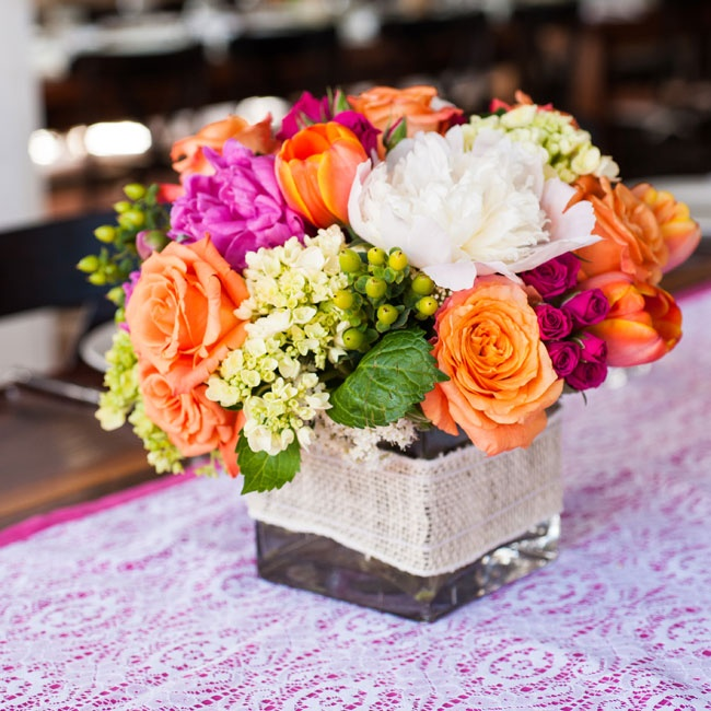 Centerpieces, held in clear vases and wrapped in burlap, contained colorful blooms like peonies, roses, freesias, and tulips.