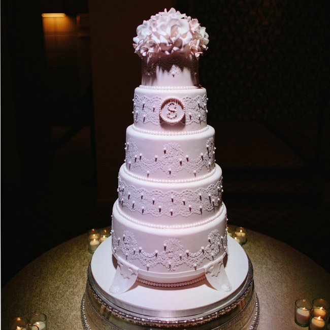Christine and Kyle's five-tier fondant cake was decorated with fondant lace and pearls for a romantic flair. A bunch of pink sugar flowers topped off the cake.