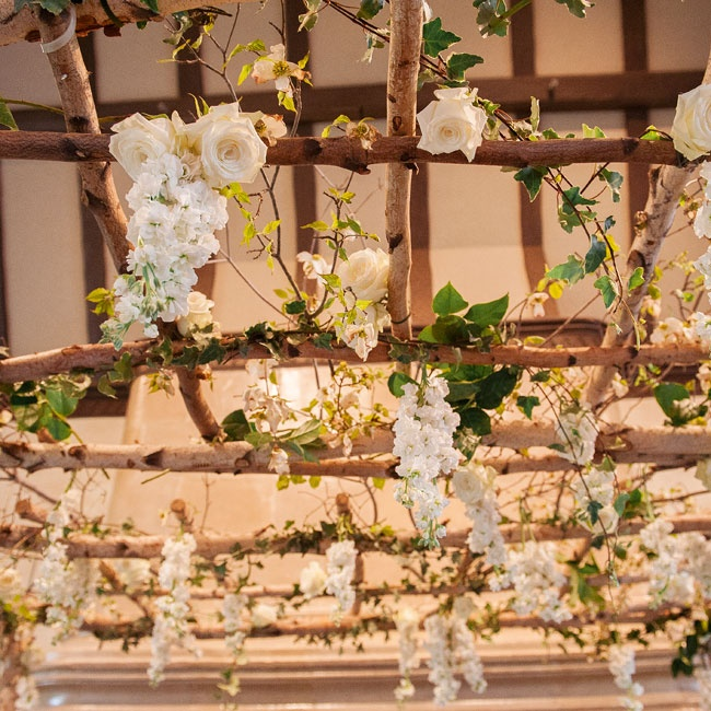 The huppah at the ceremony had a rustic look with sparse branches and white flowers.