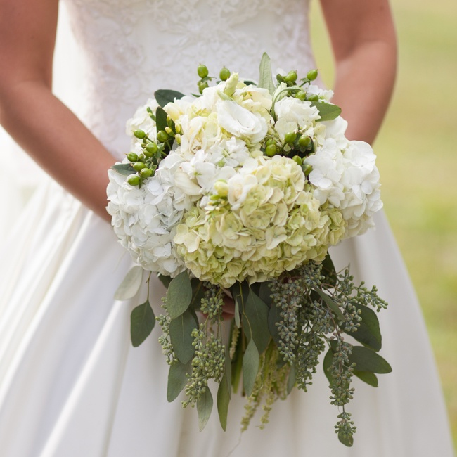 Ashlie's bridal bouquet was filled with white and pale green hydrangeas, accented by eucalyptus and bright green coffee berries.