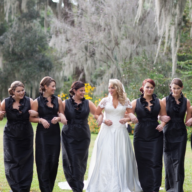 Ashlie's bridesmaids wore floor-length black gowns in a sheath style with high ruffled collars to go with the formal black-and-white themed wedding.