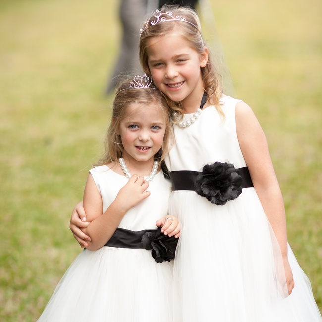 The flower girls donned white dresses with tulle skirts and black satin bows with a floral detail, keeping with the black and white theme. They finished the look with strings of pearls and tiaras.