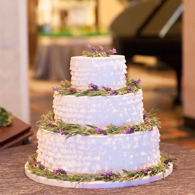 The three-tiered wedding cake was created by Sweet Sisters and was adorned with real flowers including rosemary for a visual affect.