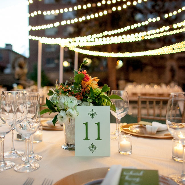 Green table numbers and bright centerpieces made from vintage mercury glass decorated the outdoor reception tables.