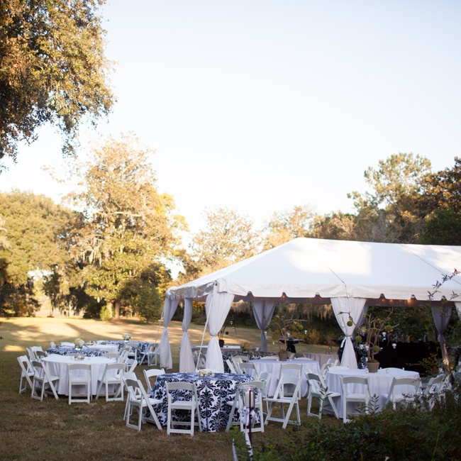 The reception was held on the sweeping lawns of the Magnolia Plantation under a white tent draped with flowing white fabric.