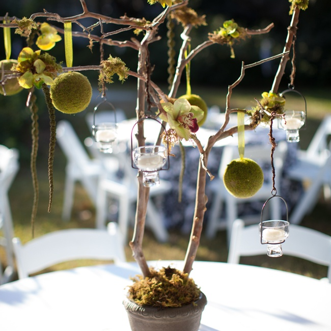 The reception tables were topped with whimsical twig centerpieces set in black urns with hanging votive candles, moss pomanders and orchids.