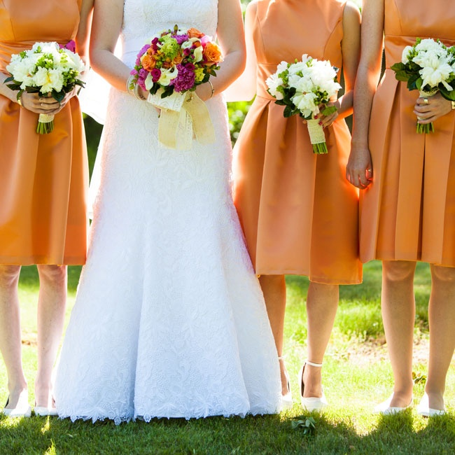 White bouquets of peonies, ranunculuses and roses popped against the ladies orange knee-length dresses.