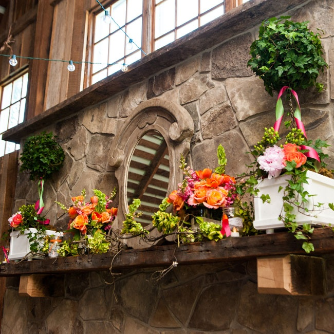 The barn's mantel was decorated with topiaries and floral arrangements in shades of orange, fuchsia and lime green.