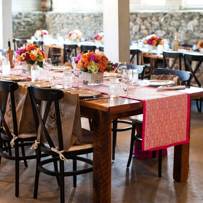 Erin had custom table runners made in New York. Each runner had a lace overlay on top of orange, fuchsia or lime cotton fabric. Colorful floral arrangements in vases wrapped with burlap completed the decor.