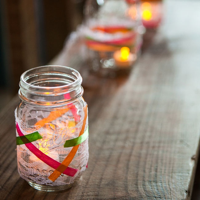 Mason jars wrapped with ribbons and lace held flameless candles during the reception.