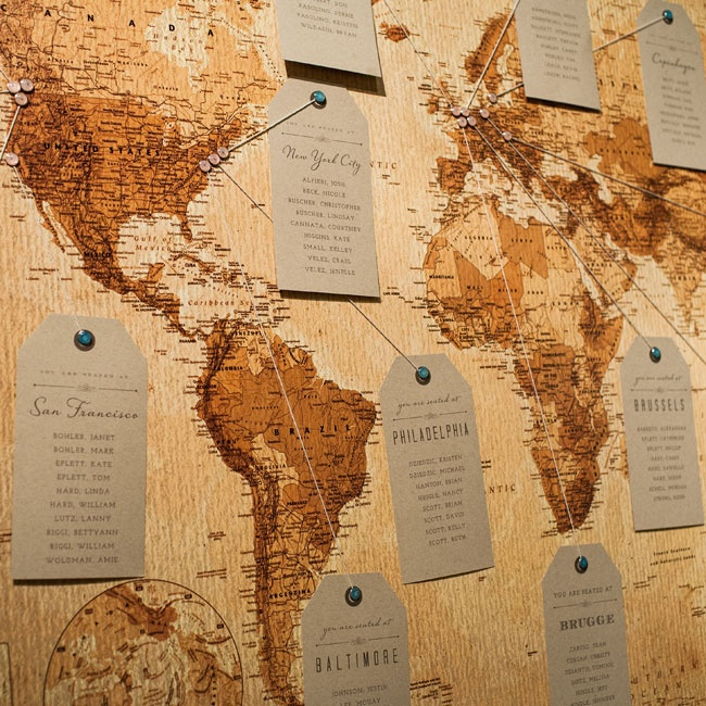 "The couple had a friend frame a vintage map, which was used as a seating chart. ""We pinned city and country names and used twine to hold each of the table names where guests were sitting,"" explains Danielle."