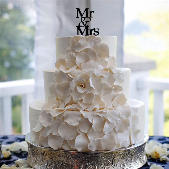 The couple chose a traditional white round cake with three tiers, accented with a deconstructed sugar flower.
