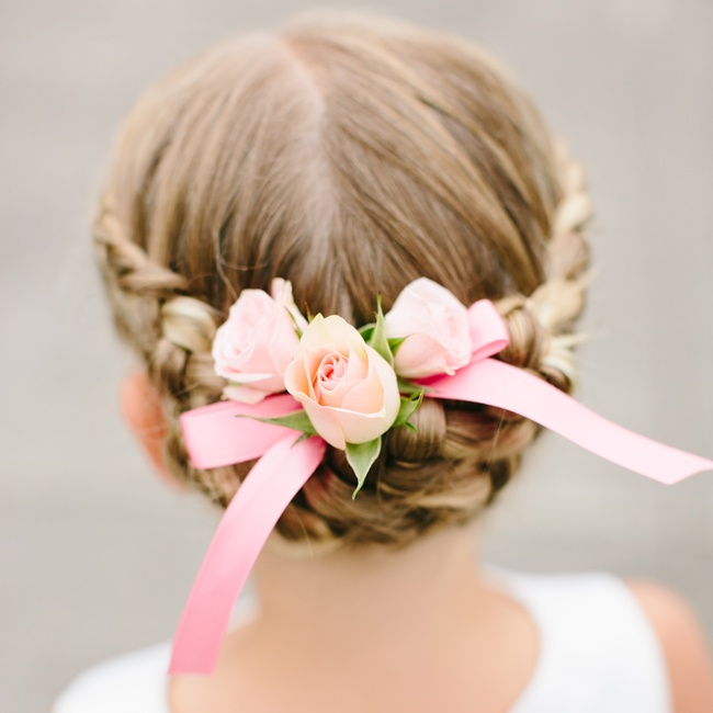 The flower girls wore their hair in braided updos, which they accented with pink roses and ribbon.