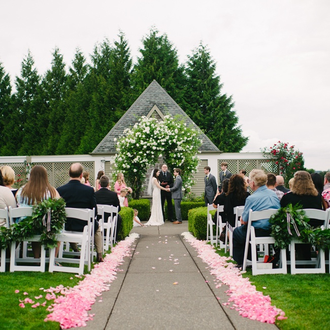 Sarah and Geoff exchanged vows in a garden ceremony at Oregon Golf Club. Pink and white rose petals were scattered down the aisle leading to an extravagant floral wedding arch.