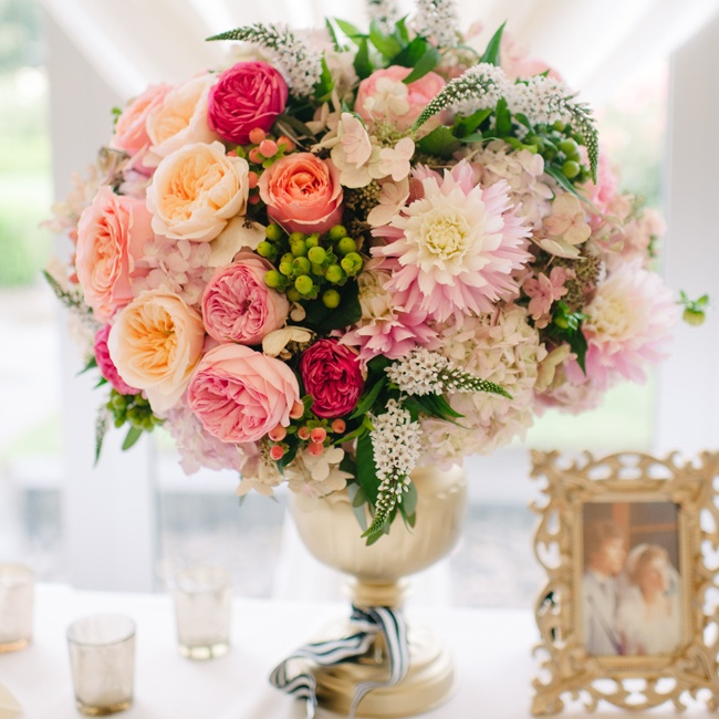 Arrangements of roses, peonies, dahlias and astilbe in peach and pink hues filled golden vases tied with black and white striped ribbon, the very same fabric used for Sarah's bouquet wrap.