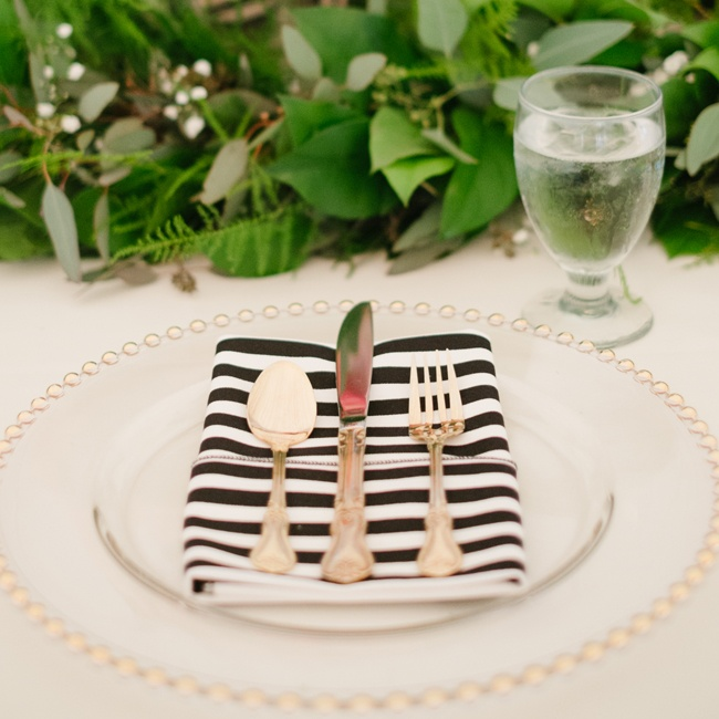 For a fun modern touch, gold studded, clear chargers were set with black and white striped linens and golden silverware.