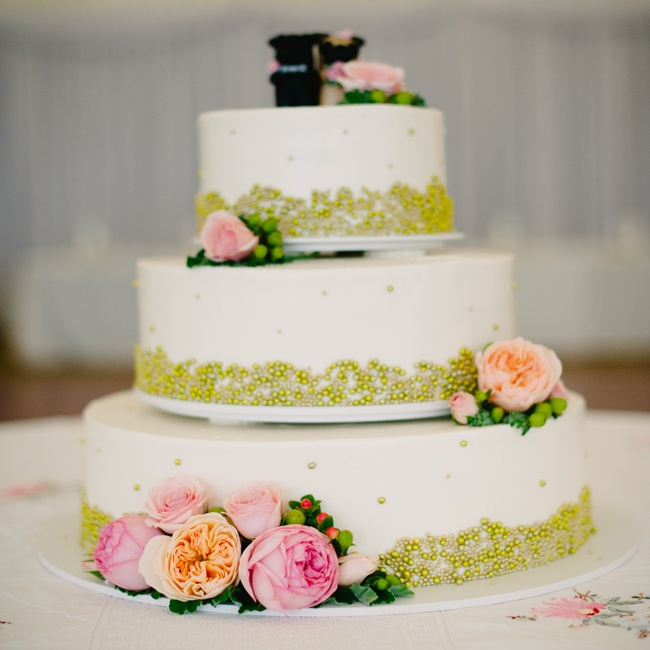 The three-tiered cake was decorated with green pearls in polka dot and wave-like patterns on each layer. Pink peonies and hypernicum berries adorned each layer for a feminine touch.