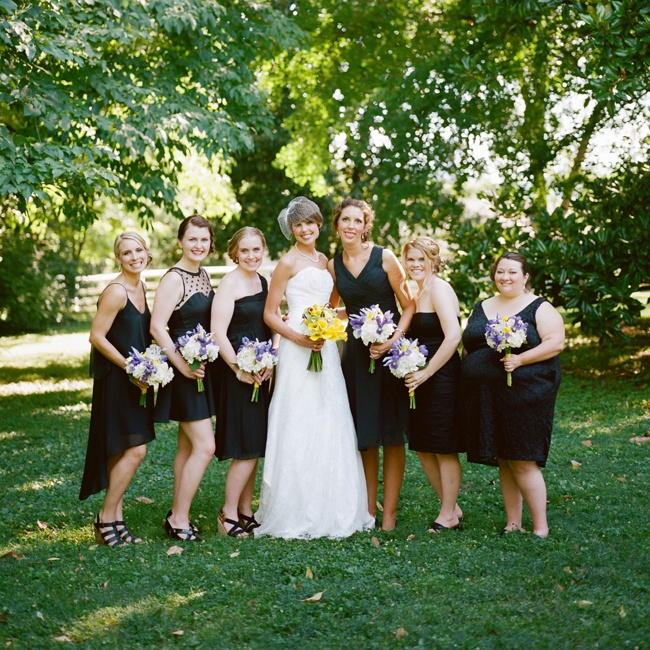 Heather's bridesmaids wore black short dresses in various styles and carried purple and white bouquets.