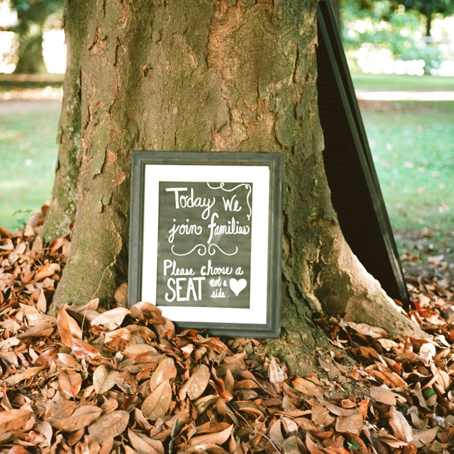"A sign sitting in newly fallen leaves informed guests to ""Please chose a seat, not a side."""