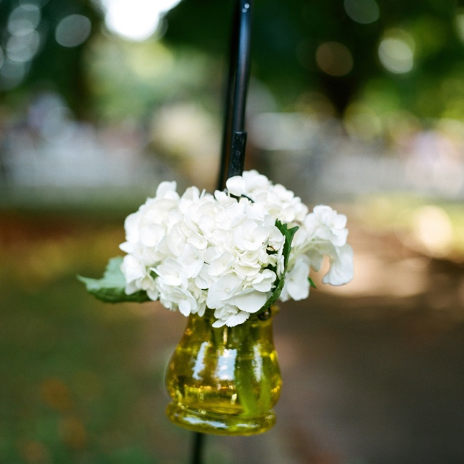 Ceremony aisles were marked with clusters of hydrangeas in yellow jars.