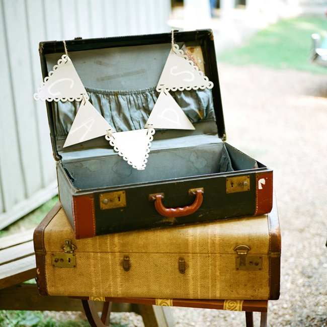 The bride and groom asked guests to place their cards in this vintage suitcase display, labeled with neutral pennants.