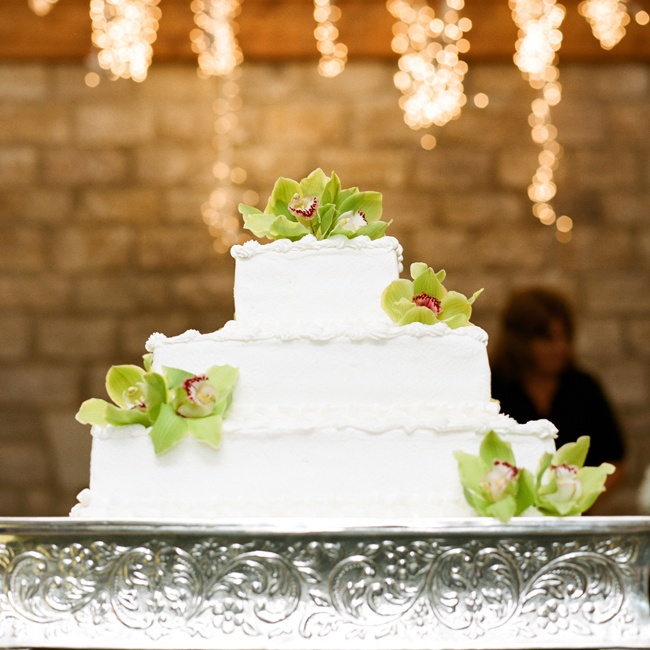 The couple's traditional white, three-tier cake was embellished with green orchid-inspired sugar flowers.