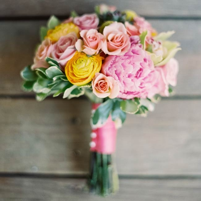 One bridal bouquet was bright yellow and pink with mostly peonies, roses and ranunculuses and wrapped in pink ribbon.