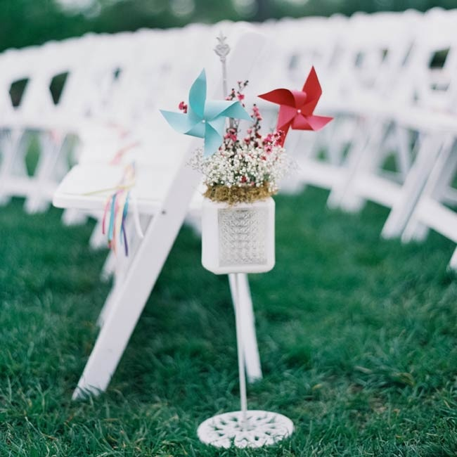 The outdoor ceremony aisles were marked with delicate flowers and colorful pinwheels.