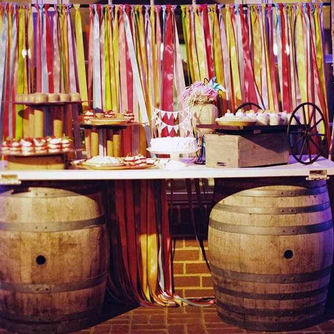 An array of desserts were displayed on a table balanced on two oak barrels against a backdrop of colorful ribbon streamers.