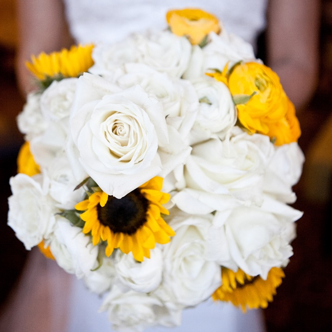 White roses mixed with bright yellow ranunculuses and sunflowers for a cheery bridal bouquet.