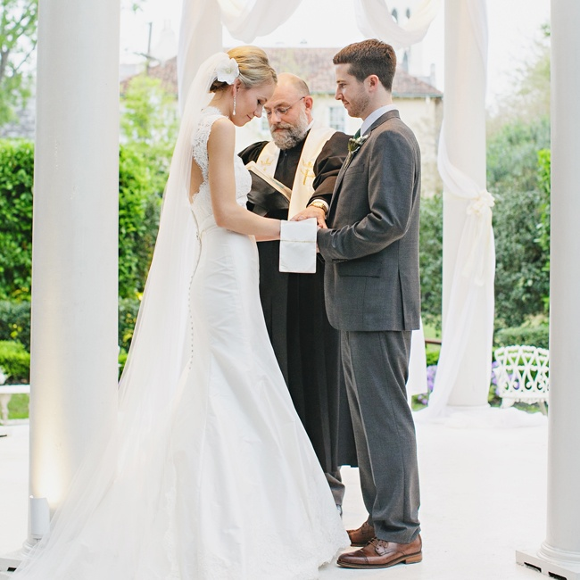 The bride wore a Paloma Blanca gown that featured lace detailing and a keyhole back, while the groom sported the J. Crew Ludlow suit.