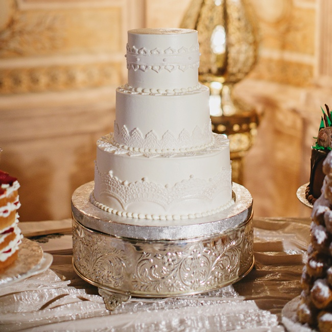 The couple took the traditional route with their wedding cake, opting for a classic white, round, tiered confection with damask fondant accents.